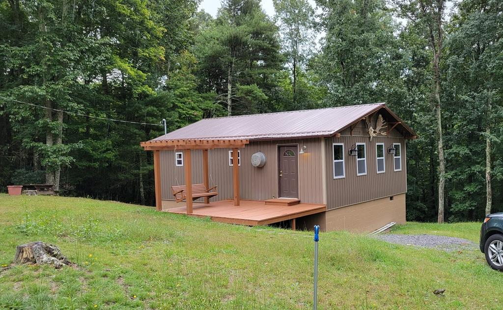 This is a truly well-built cabin on a 3.06 acre beautiful and peaceful setting. To begin at the entrance we cross a well-designed, wooden open porch complete with a pergola and swing. We enter into a sunroom that is 73 x 235 with nice tile flooring. From here we enter the combination family room, kitchen, and dining area which is 114 x 227. Next, there is a bedroom to the right and a bedroom to the left with the bath in between. Move-in ready. With a few exceptions, all furnishings, electronics, and appliances convey with property. This home has full insulation, wood floors, metal roof, a full crawlspace with a new water heater and lots of storage. Buyer to determine internet availability. This is a must see property.  Call listing agent for showing.